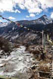 与雪的黑山在上面 在地面上是有石头、冰、黄色草和西藏人祷告旗子的冻河 库存照片