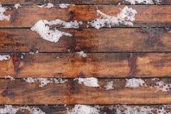 与雪盖的木地板的冬天背景 免版税库存照片