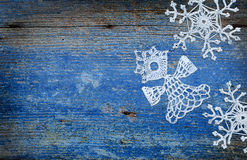 与雪花和天使的蓝色木背景 库存图片