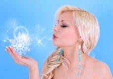 与雪花和星形的少妇吹的亲吻在蓝色 免版税图库摄影