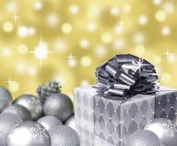 与雪花和金抽象bokeh背景的银色当前弓和圣诞节球 免版税库存图片