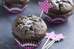 与雪花的巧克力杯形蛋糕在桃红色小篓 库存照片