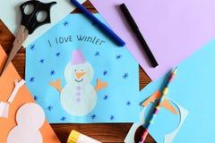 与雪花的雪人纸牌和词我爱冬天 儿童冬天工艺的材料 库存照片