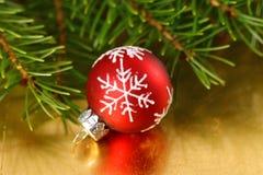 与雪花装饰品的圣诞节红色中看不中用的物品在金背景 免版税库存照片