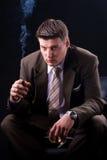 与雪茄和饮料的富有的生意人 免版税库存照片