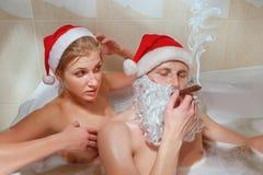 与雪茄和他的女朋友的圣诞老人。 库存图片
