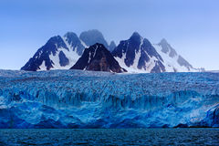 与雪,与海前景的,斯瓦尔巴特群岛,挪威,欧洲的蓝色冰川冰的黑暗的冬天山 免版税图库摄影