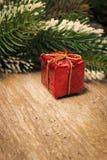 与雪,在葡萄酒木桌上的红色礼物盒的云杉的分支 图库摄影