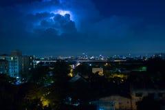 与雷击的暴风云闩上通过在夜城市 免版税库存照片