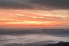与雾的多数多云日出在谷 免版税库存照片