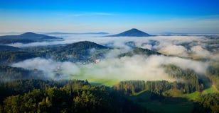 与雾的捷克典型的夏天风景 小山和村庄与有雾的早晨 早晨漂泊瑞士公园秋天谷  免版税库存照片