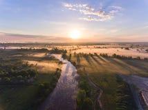与雾的空中日出在树在农村乡下冠上 免版税库存图片