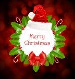 与霍莉、甜点、圣诞老人帽子和红色弓的圣诞节花圈 免版税图库摄影