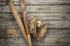 与露指手套和棒的老棒球在粗砺的木头 库存图片