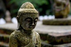 与青苔关闭的石菩萨雕象 图库摄影