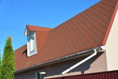 与青苔的老屋顶沥青木瓦 雨与水落管管子和顶楼有双重斜坡屋顶的房屋窗口的天沟管道 库存照片