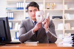 与面具的商人在办公室伪善概念 库存图片