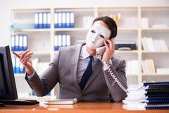与面具的商人在办公室伪善概念 图库摄影