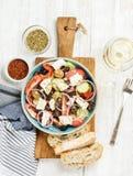 与面包切片、牛至、胡椒和白葡萄酒的希腊沙拉 图库摄影