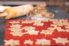 与面团卷的星状桂香圣诞节曲奇饼在背景中 免版税库存照片