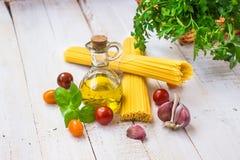 与面团成份的意大利晚餐在木厨房用桌,意粉,橄榄油,西红柿,大蒜,蓬蒿,荷兰芹上 库存图片
