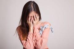 与面对的棕榈的哀伤的年轻亚洲妇女啼声 库存照片