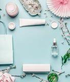 与面部化妆产品、购物袋和枝杈的秀丽背景有在淡色蓝色桌面背景的樱花的 免版税库存图片