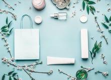 与面部化妆产品、购物袋和樱花的秀丽概念在淡色蓝色桌面上 免版税图库摄影