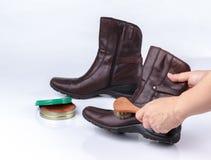 与鞋子刷子的妇女的手擦亮的起动 库存图片