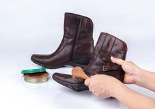 与鞋子刷子的妇女的手擦亮的起动 图库摄影
