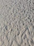 与鞋子印刷品的白色沙子 免版税库存照片