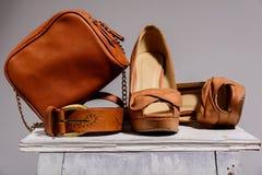 与鞋子和传送带的布朗女性袋子 免版税库存图片