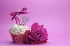 与鞋子和心脏装饰的紫红色的桃红色题材杯形蛋糕 免版税库存照片