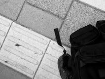 与鞋子的袋子在与引导的瓦片的驻地瞎的人民的 库存图片