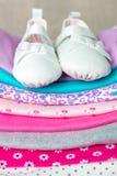 与鞋子的被折叠的桃红色和白色紧身衣裤对此灰色木背景 新出生的女孩的尿布 堆婴儿衣物 孩子 图库摄影