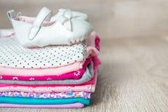 与鞋子的被折叠的桃红色和白色紧身衣裤对此灰色木背景 新出生的女孩的尿布 堆婴儿衣物 孩子 库存图片