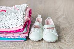 与鞋子的被折叠的桃红色和白色紧身衣裤对此灰色木背景 新出生的女孩的尿布 堆婴儿衣物 孩子 库存照片
