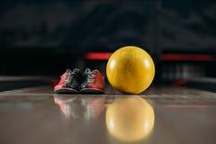 与鞋子的黄色保龄球在胡同 免版税库存照片