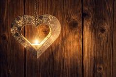 与鞋带设计的蜡烛台与里面茶蜡烛,在木背景,华伦泰的浪漫背景的蜡烛台或婚姻 库存图片