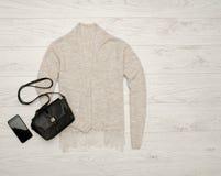 与鞋带,黑提包,电话的灰色米黄羊毛衫 秀丽蓝色聪慧的概念表面方式构成妇女 顶视图,文本的空间 免版税图库摄影