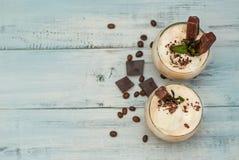 与鞭子奶油,夏天饮用的时间的被冰的上等咖啡Frappe咖啡 在白色的豆早餐咖啡理想的查出的宏指令 土气织地不很细木背景 薄荷叶拷贝 免版税库存图片