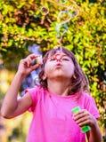 与鞭子的小女孩吹的泡影在公园 免版税库存照片