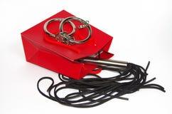 与鞭打的鞭子和手铐的红色购物袋 免版税图库摄影