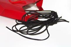 与鞭打的鞭子的红色购物袋 免版税图库摄影