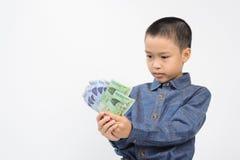 年轻与韩国被赢取的钞票的男孩以愉快和微笑 免版税库存照片