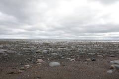 与顶上的云彩的平的多岩石的海滩场面 库存照片