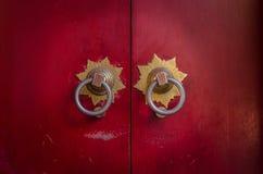 与顶头金属敲门人的老朱红色的门 免版税库存照片