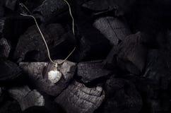 与项链的银色心脏形状小盒在黑木炭textu 免版税库存图片