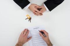 与顾客签署的合同的房地产开发商在书桌 免版税库存照片