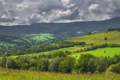 与领域、多云天空和村庄的夏日风景 库存照片